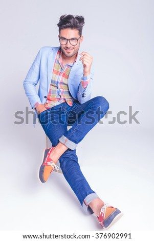 handsome casual man posing seated with legs crossed and hand in pocket while looking at the camera in studio background