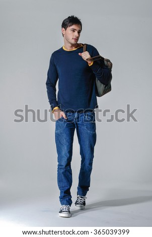 Handsome casual man smiling with bag walking in studio