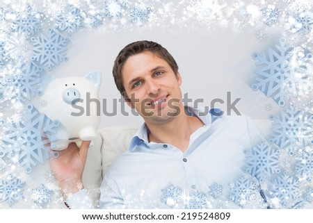 Handsome casual man with piggy bank in living room against snow - stock photo
