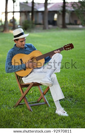 Handsome casual middle aged man playing guitar in park - stock photo