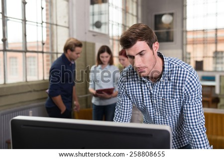 Handsome casual young businessman standing working at a monitor in an office as his colleagues stand talking in the background - stock photo