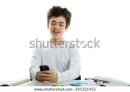 Handsome Caucasian boy sits in front of homework wearing a white long sleeve t-shirt and smiles using his cell phone, a smartphone - stock photo