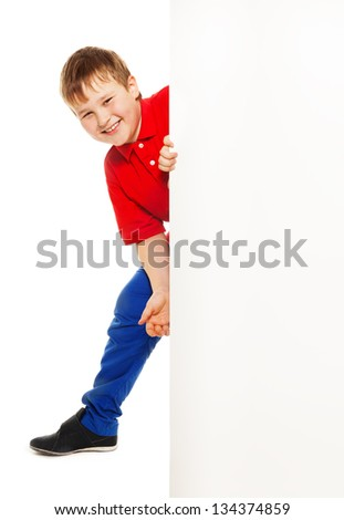 Handsome Caucasian boy, standing and smiling looking from behind white placard, isolated on white - stock photo