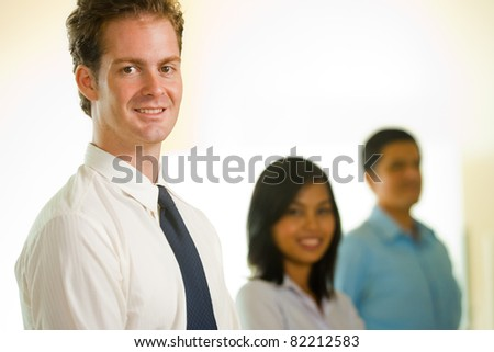 Handsome Caucasian British businessman angled portrait looking at camera leading a team of colleagues including Asian female and Latino male lined up standing in a row. Horizontal