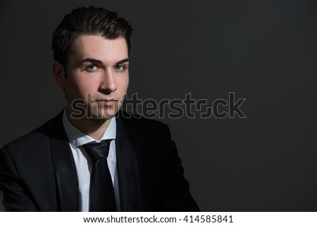 Handsome caucasian businessman in suit on dark background - stock photo