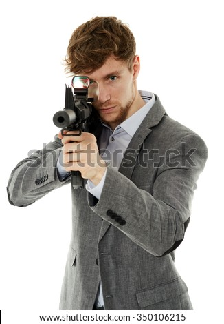 Handsome caucasian guy aiming the machine gun at invisible target isolated on white