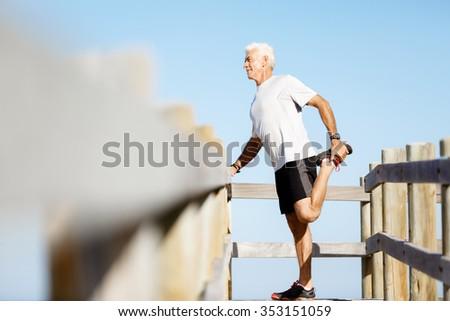 Handsome caucasian male doing exercises on beach - stock photo