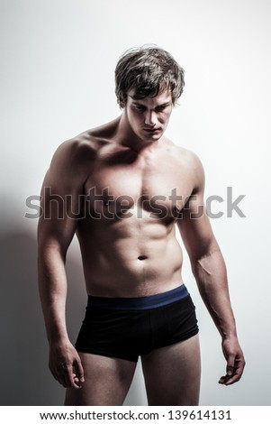 handsome caucasian male model in the studio wearing black and blue underwear - stock photo