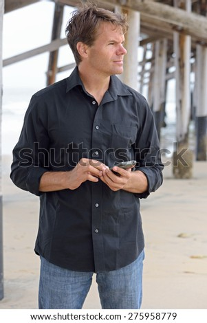 Handsome Caucasian man in casual clothing standing under pier at beach using smart phone as he waits to meet someone - stock photo