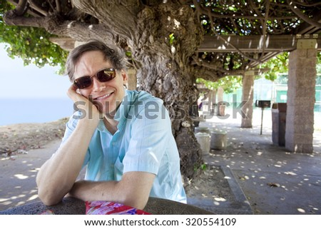 Handsome Caucasian man in forties relaxing under shaded tree canopy by ocean, smiling head on hand - stock photo