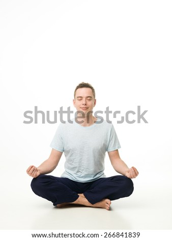 handsome caucasian man sitting in lotus position, meditating on white studio floor