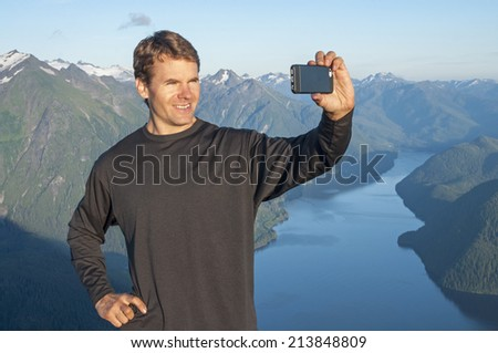 Handsome Caucasian man smiles as he poses for selfie portrait on top of mountain with beautiful scenic view - stock photo