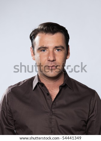 Handsome caucasian man smiling portrait on grey isolated background with brown shir - stock photo