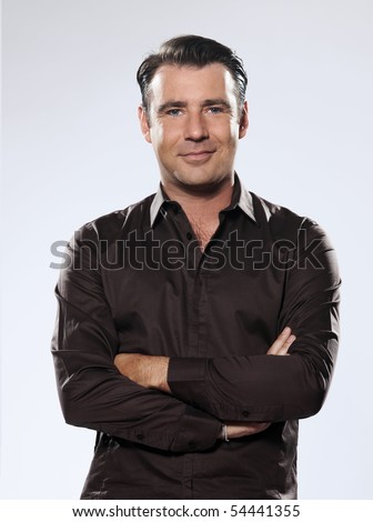 Handsome caucasian man smiling portrait on grey isolated background with brown shirt