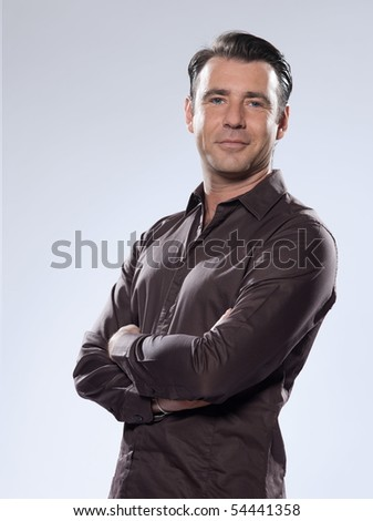 Handsome caucasian man smiling portrait on grey isolated background with brown shirt - stock photo