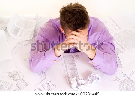 Handsome Caucasian man very emotional in the papers on a light background - stock photo