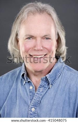 handsome caucasian man wearing blue shirt on grey background - stock photo