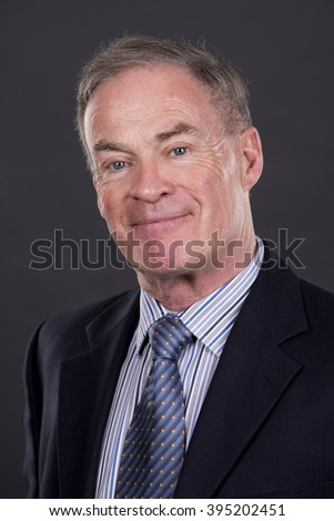 handsome caucasian man wearing business suit on dark background - stock photo