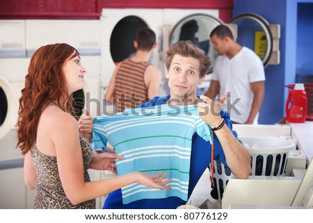 Handsome Caucasian man with his girlfriend stretches shrunk t-shirt in laundromat - stock photo