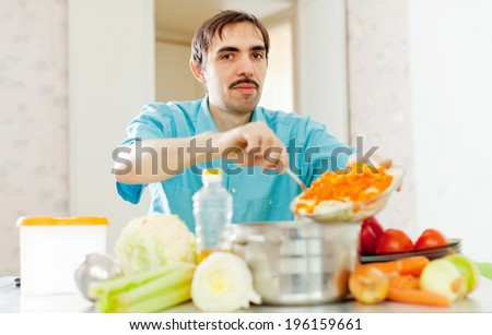 handsome caucasian man with vegetables on cutting board   - stock photo
