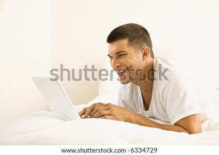 Handsome Caucasian mid adult man lying in bed with laptop. - stock photo