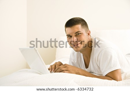 Handsome Caucasian mid adult man lying in bed with laptop looking at viewer. - stock photo