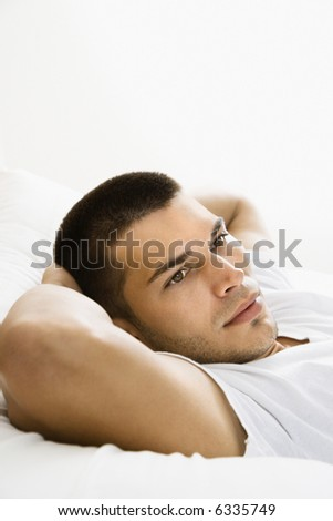Handsome Caucasian mid adult man lying with hands behind head. - stock photo