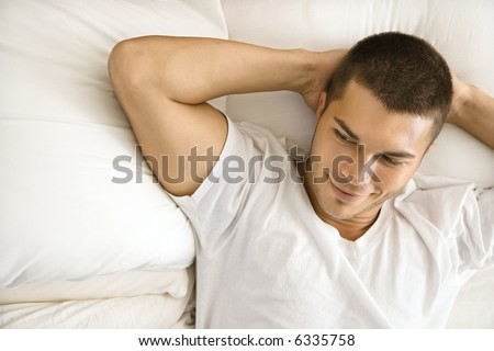 Handsome Caucasian mid adult man lying with hands behind head smiling. - stock photo