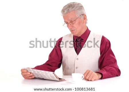Handsome caucasian nice senior male sits at a table with a newspaper on a light background