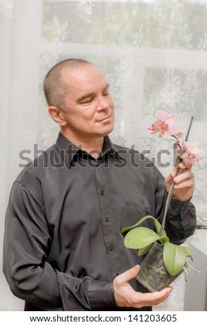 Handsome caucasian 40s man smiling portrait on grey background with black shirt holding orchid in pot and looking at this plant. - stock photo