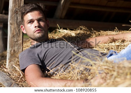 Handsome caucasian young man in the hay barn - stock photo