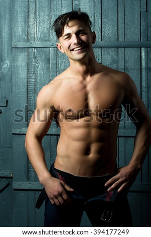 Handsome cheerful happy smiling young man brunet shirtless with amazing sexy muscular bare torso dressed in unbutton black trousers standing with hands on hips on gray background studio, vertical - stock photo
