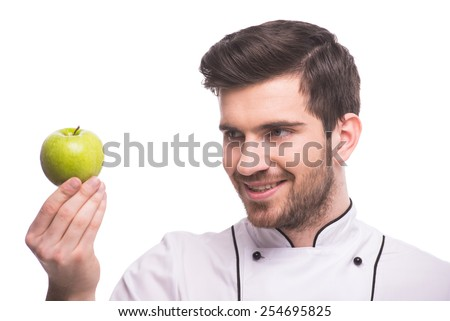 Handsome chef is holding an apple, isolated on white background.