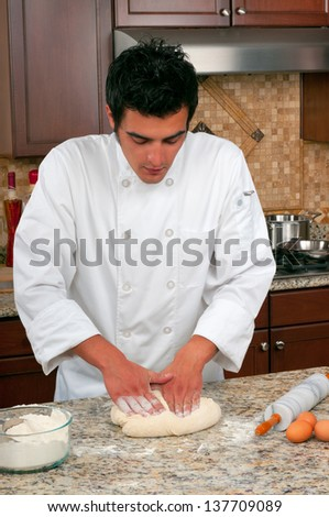 Handsome chef making bread or pasta - stock photo