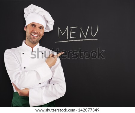 Handsome chef showing menu - stock photo