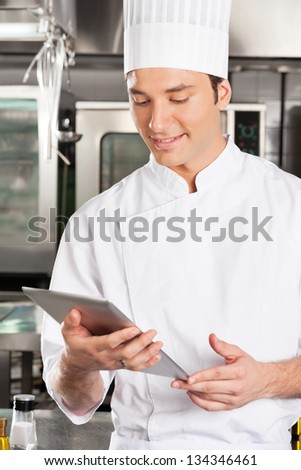 Handsome chef using digital tablet in commercial kitchen