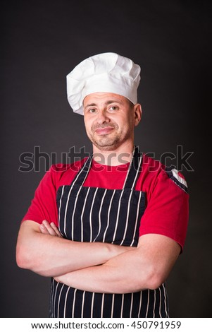 Handsome chef with crossed arms posing against black background - stock photo