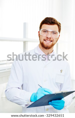 Handsome chemist in white-coat, eyeglasses and gloves making notes in lab - stock photo