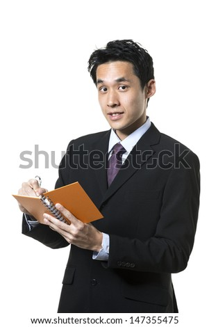 Handsome Chinese business man taking notes. Isolated on a white background.
