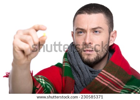Handsome cold man in a warm blanket, is holding a pills. - stock photo