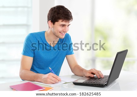Handsome college student using his laptop computer in the campus - stock photo