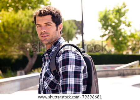 Handsome college student with a backpack smiling.