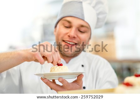 Handsome confectioner in uniform decorating cake with currant  - stock photo