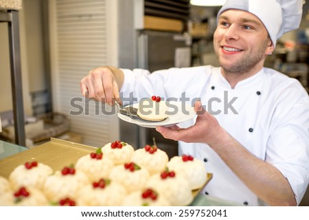 Handsome confectioner selling cakes in the pastry shop - stock photo