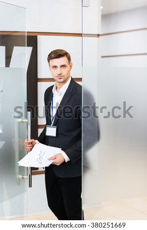 Handsome confident businessman in black suit entering the office