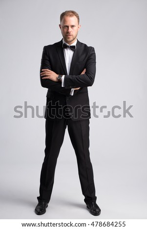 Handsome confident businessman in classic suit on gray background