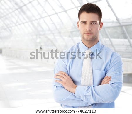 Handsome confident businessman standing at modern office lobby arms crossed.? - stock photo