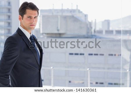 Handsome confident businessman standing in his office - stock photo
