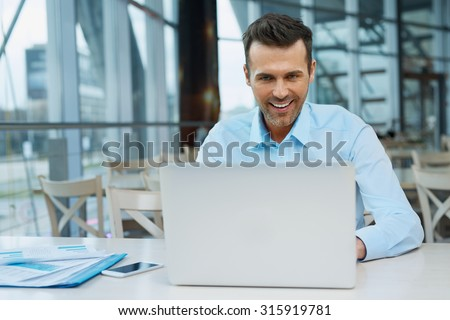 Handsome confident businessman working at modern office on laptop - stock photo