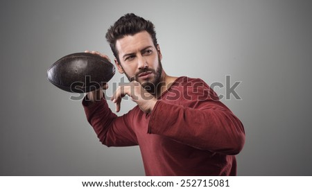 Handsome confident football player in red t-shirt launching ball - stock photo